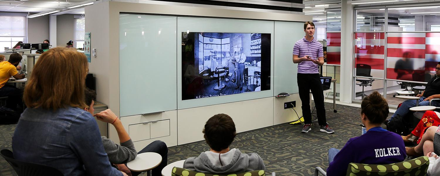 Image of a student speaking to a large class in a public space